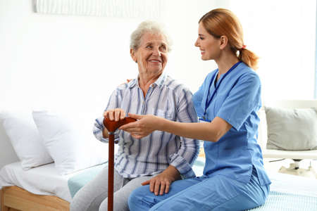 Enfermera en uniforme ayudando a anciana en interiores Foto de archivo