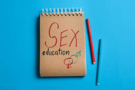 Notebook with phrase SEX EDUCATION and gender symbols on blue background, flat lay