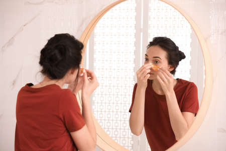 Young woman with eye patches near mirror in bathroom