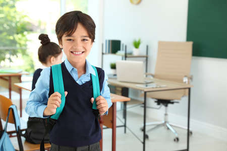 Boy wearing school uniform with backpack in classroom