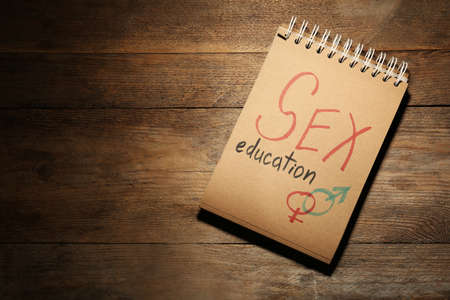 Notebook with phrase SEX EDUCATION and gender symbols on wooden background, top view. Space for text Stock Photo