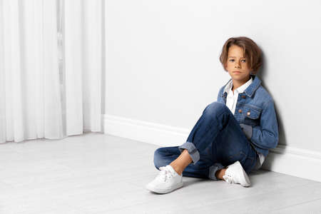Cute little boy in casual outfit near white wall in room. Space for text Zdjęcie Seryjne