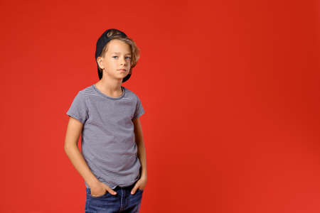 Cute little boy in casual outfit on red background. Space for text Zdjęcie Seryjne