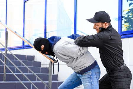 Police officer arresting masked criminal outdoors
