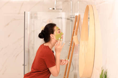 Young woman applying mask on her face near mirror in bathroom