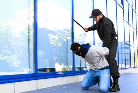 Police officer with baton arresting masked criminal outdoors Banco de Imagens