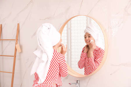 Young woman with towel on head near mirror in bathroom