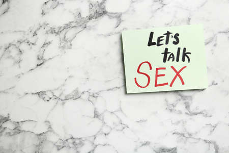 Note with phrase LETS TALK SEX on marble background, top view. Space for text