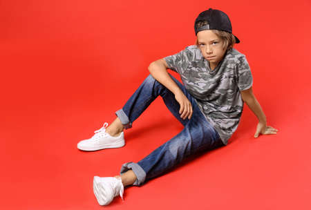 Cute little boy in casual outfit on red background