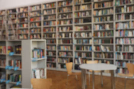 Blurred view of bookshelves and table in library