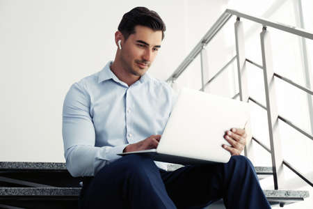 Portrait of young man with laptop indoors