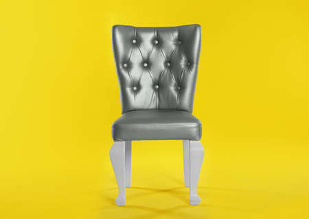 Stylish silver chair on yellow background. Element of interior design Stockfoto - 130558732