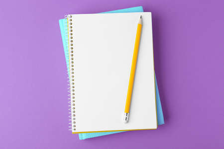 Notebooks with pencil on purple background, top view