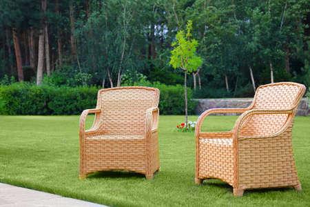 Garden rattan armchairs on green grass at backyard
