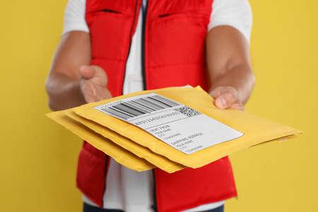 Jeune courrier avec des enveloppes sur fond jaune, gros plan