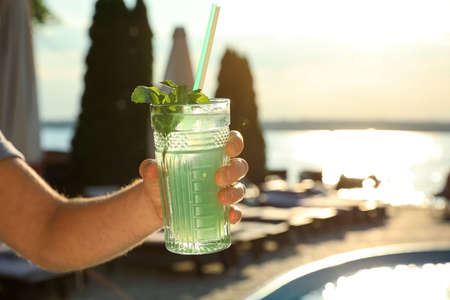 Man with glass of fresh summer cocktail near swimming pool outdoors at sunset, closeup. Space for text