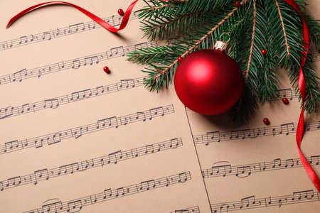 Flat lay composition with Christmas decorations on music sheets, space for text Stock Photo