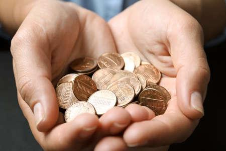Giovane donna che tiene monete su sfondo nero, primo piano