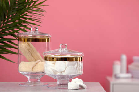Composition of glass jars with cotton pads on table against pink background. Space for text