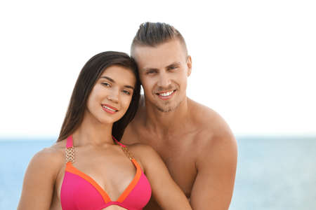 Young woman in bikini spending time with her boyfriend on beach. Lovely couple Stock Photo