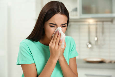 Young woman suffering from allergy in kitchen
