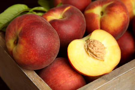 Tasty peaches and leaves in wooden crate, closeup 版權商用圖片 - 130494224
