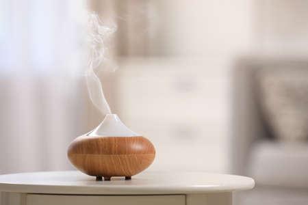 Diffuseur d'huiles essentielles moderne sur table à l'intérieur. Espace pour le texte Banque d'images