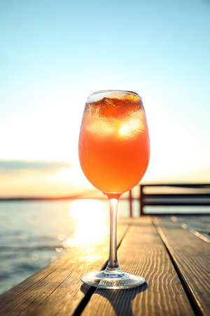 Glass of fresh summer cocktail on wooden table outdoors at sunset Foto de archivo