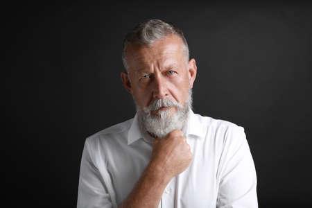 Portrait of handsome senior man on black background