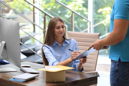 Frau, die am Tisch im Büro für gelieferte Pakete unterschreibt