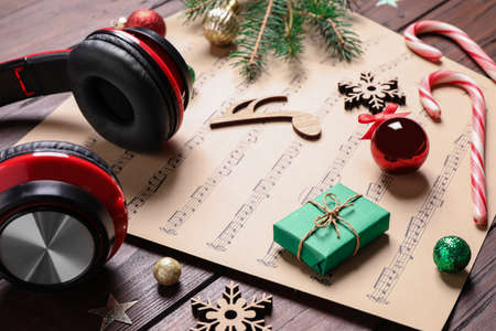 Christmas decorations, headphones and music sheets on wooden table Stock Photo