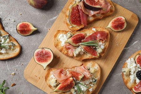 Bruschettas with cheese, prosciutto and figs served on marble table, top view