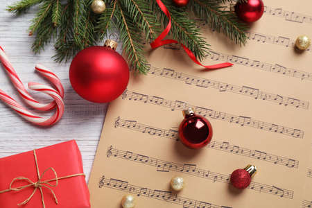 Flat lay composition with Christmas decorations and music sheets on white wooden table