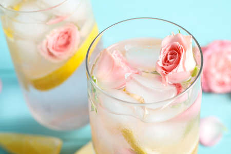Tasty refreshing lemon drink with roses on light blue table, closeup