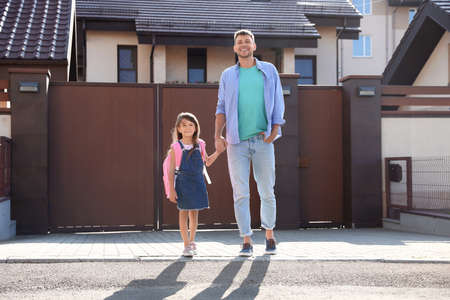 Happy father taking his little child to school on street