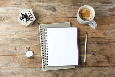 Flat lay composition with office stationery and cup of coffee on wooden table. Space for design