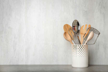 Holder with kitchen utensils on grey table against light background. Space for text