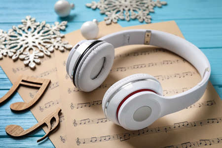 Christmas decorations, headphones and music sheets on blue wooden table, closeup Stock Photo
