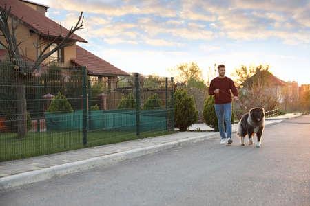 Young man walking his Caucasian Shepherd dog outdoors Archivio Fotografico - 130804262