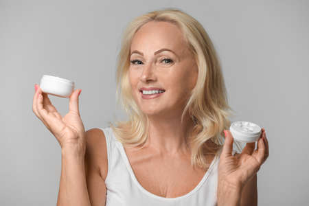 Portrait of beautiful mature woman with perfect skin holding jars of cream on grey background Фото со стока