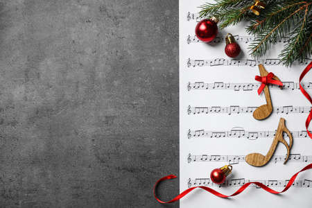 Christmas decorations, notes and music sheet on grey stone table, flat lay with space for text Stock Photo