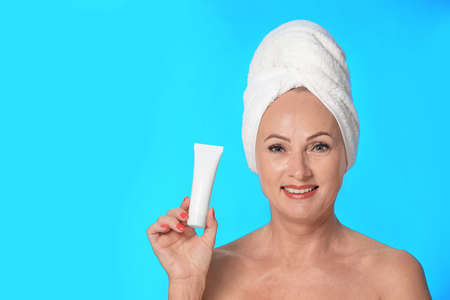 Portrait of beautiful mature woman with perfect skin holding tube of cream on light blue background