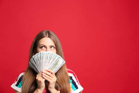 Portrait of thoughtful lottery winner with money on red background, space for text