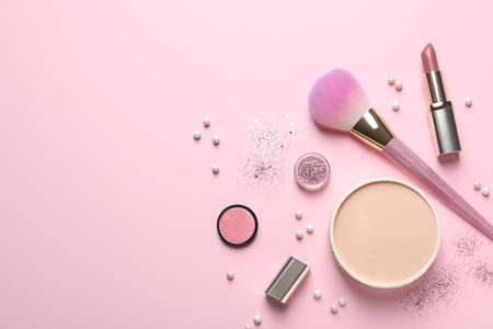Flat lay composition with makeup brushes on pink background. Space for text
