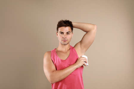 Young man applying deodorant to armpit on beige background Stock Photo