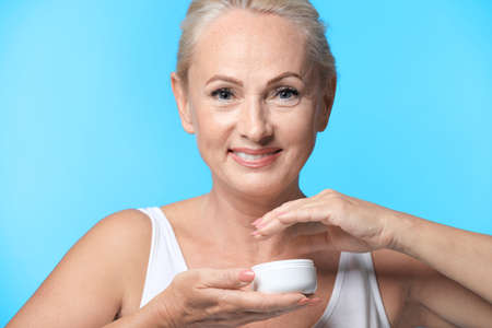 Portrait of beautiful mature woman with perfect skin holding jar of cream on light blue background Banco de Imagens
