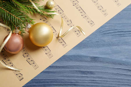 Flat lay composition with Christmas decorations and music sheets on blue wooden table. Space for text