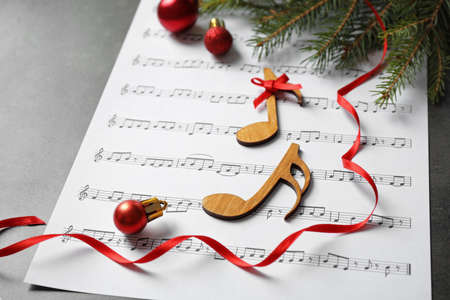 Christmas decorations, notes and music sheet on grey stone table Stock Photo