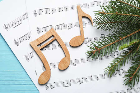 Christmas tree branch, notes and music sheets on blue wooden table, flat lay Stock Photo