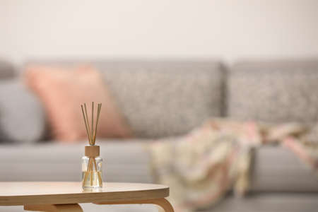 Reed air freshener with essential oil on table indoors. Space for text